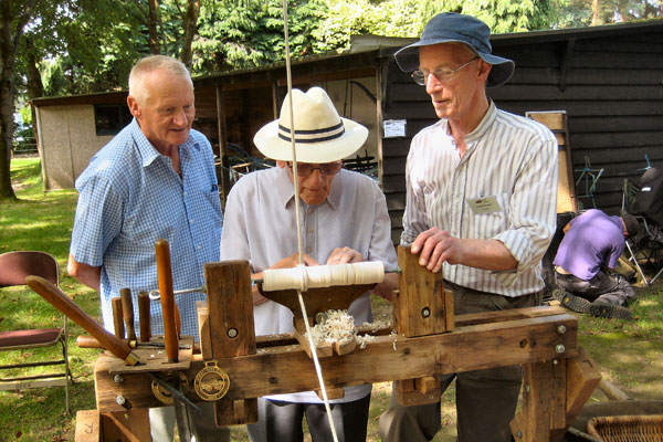 Rural Life Living Museum - Group of three mean working on vintage tools on rustic sunday
